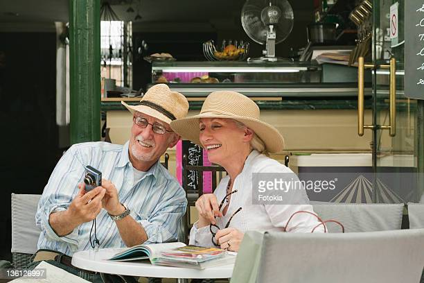 couple sharing photos over lunch. - guy carcassonne photos et images de collection