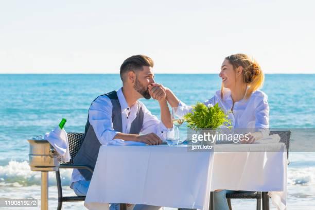 couple sharing romantic dinner beach valentines