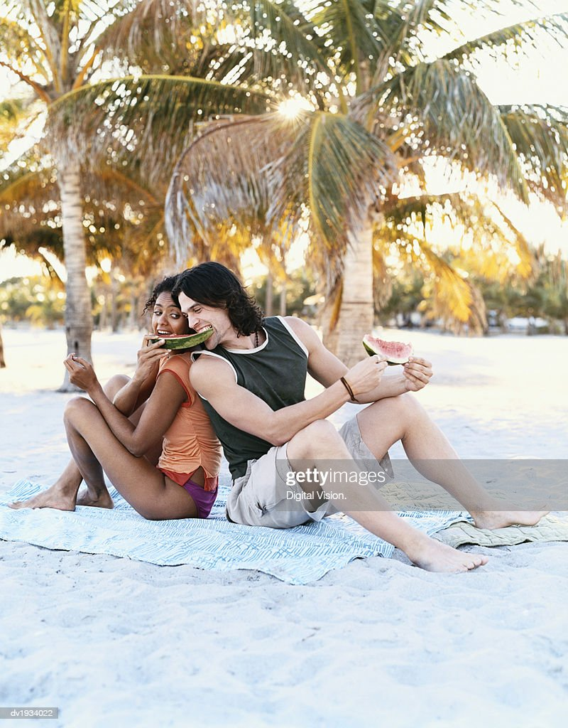 Couple Sharing Slices of Water Melon on a Beach : Stock Photo
