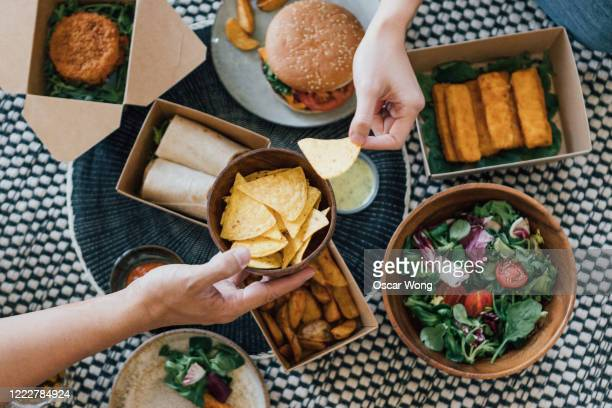 couple sharing takeaway food at home - food stock pictures, royalty-free photos & images