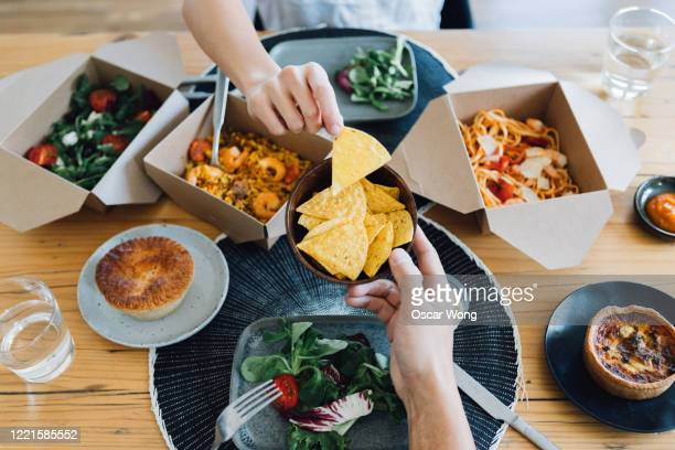 couple sharing takeaway meal at dining table - elevated view stock pictures, royalty-free photos & images