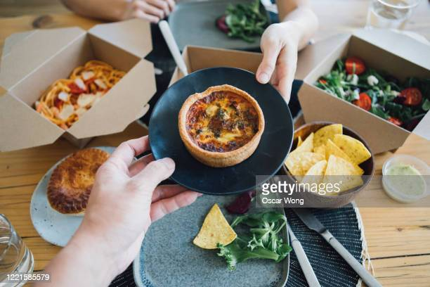 couple sharing takeaway meal at dining table - passing giving stock pictures, royalty-free photos & images