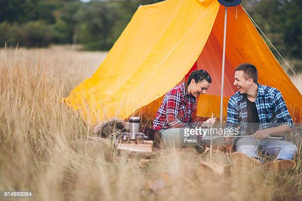 Couple sharpening wood sticks on camping for marshmallow