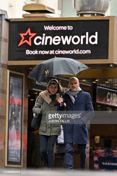 A couple shelter from the rain under an umbrella as they pass a cineworld cinema in Leicester Square in central London on October 4 2020 Cineworld is...