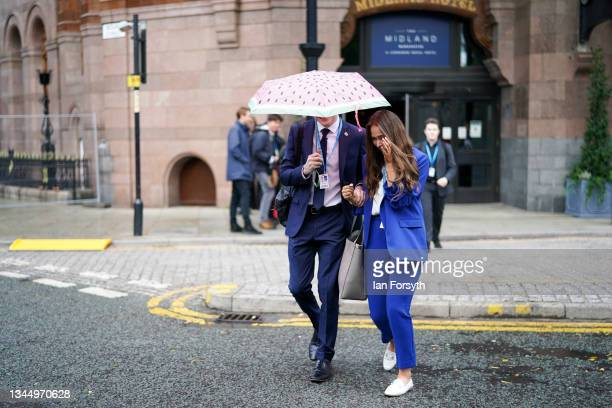 Couple shelter under an umbrella as they attend the third day of the Conservative Party Conference at Manchester Central Convention Complex on...