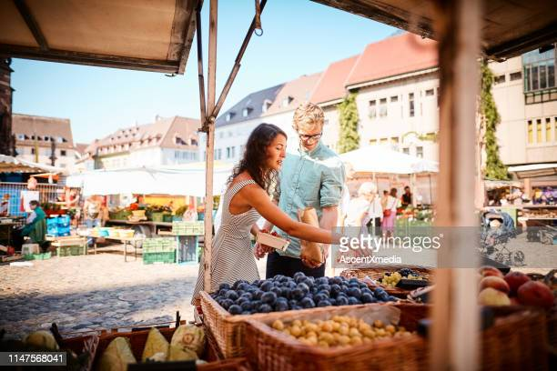 couple shop at outdoor summer fruit market - germany stock pictures, royalty-free photos & images