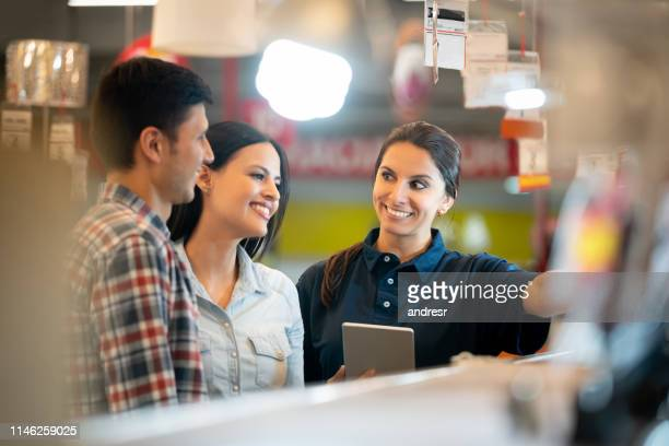 couple shopping at a home improvement store and talking to a saleswoman - assistant stock pictures, royalty-free photos & images