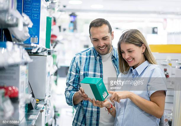 couple shopping at an electronics store - electronics store stock photos and pictures