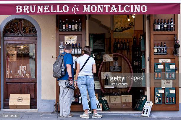 Couple shopping at Brunello Di Montalcino wine shop in ancient hill town of Montalcino in Val D'Orcia Tuscany Italy
