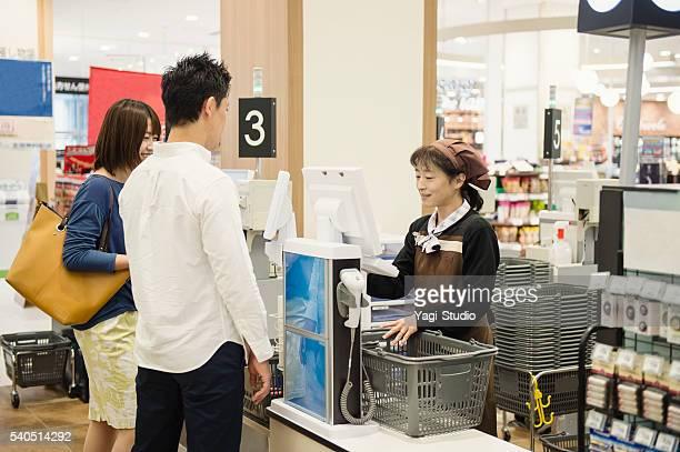 カップルショッピングには、現金のスーパーマーケットの登録