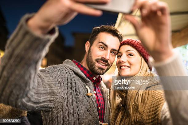 couple shopping at the christmas market take a selfie