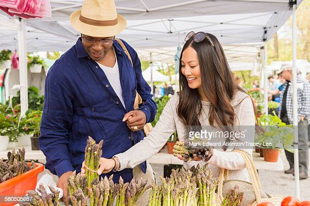 Couple shopping for asparagus in farmers market