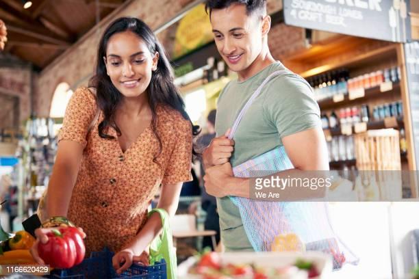 couple shopping for fresh food in plastic free market - ファーマーズマーケット ストックフォトと画像