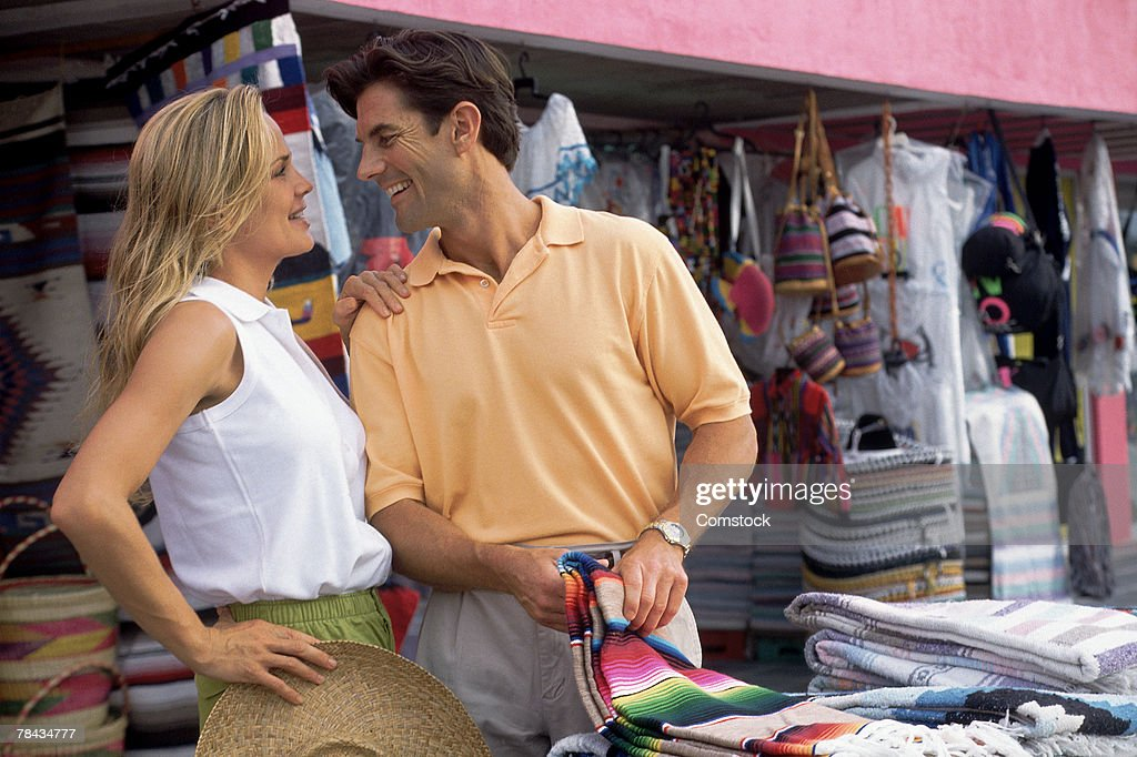 Couple shopping for souvenirs in outdoor marketplace : Stockfoto