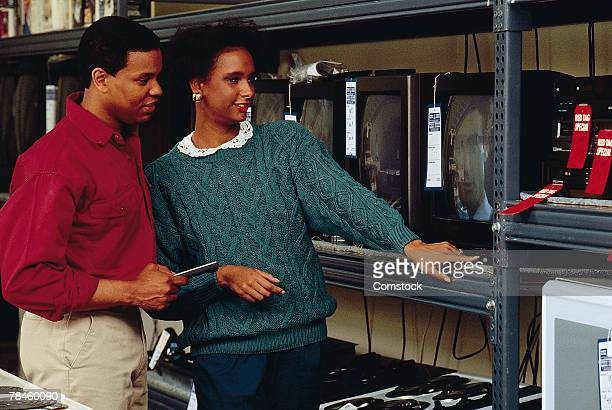 Couple shopping for television sets in store