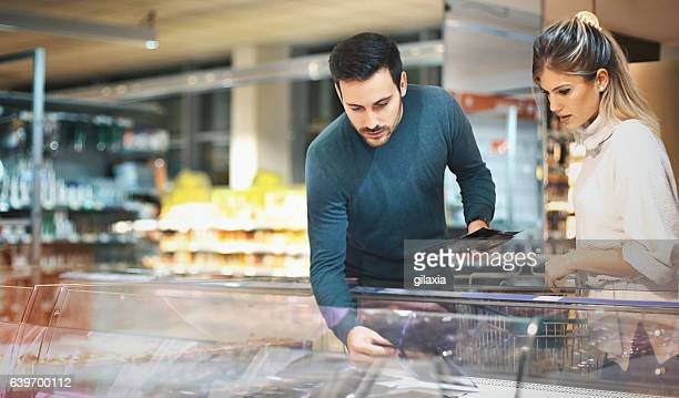 couple shopping in supermarket. - fish love stock pictures, royalty-free photos & images