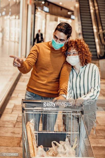 couple shopping in supermarket wearing hygienic mask to prevent the virus - micro organism stock pictures, royalty-free photos & images
