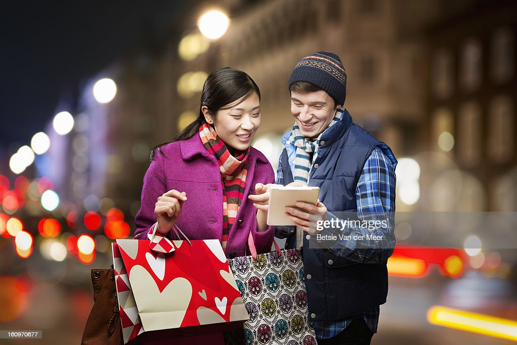 Couple shopping,looking at wireless device in city : Foto de stock