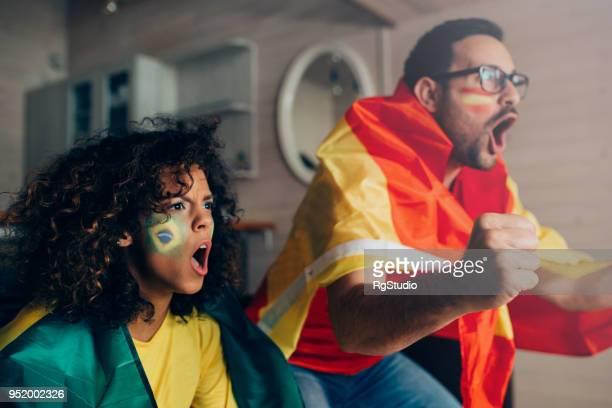 paar schreien beim fußballspiel im fernsehen ansehen - weltmeisterschaft stock-fotos und bilder