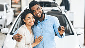 Couple Showing New Car Key Smiling In Dealership Showroom, Panorama