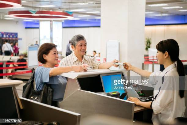 couple showing passports at airport check-in counter - verification stock pictures, royalty-free photos & images