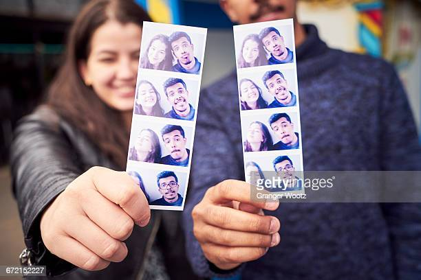 Couple showing photograph strips from photo booth