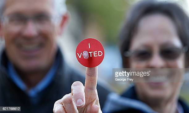 A couple shows off their I Voted sticker as they leave Wasatch Elementary school after casting their ballot in the presidential election on November...