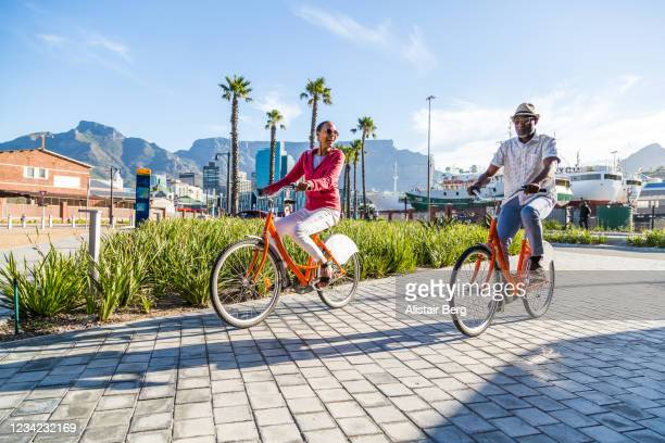 couple sightseeing on hired bicycles in city - disruptaging foto e immagini stock