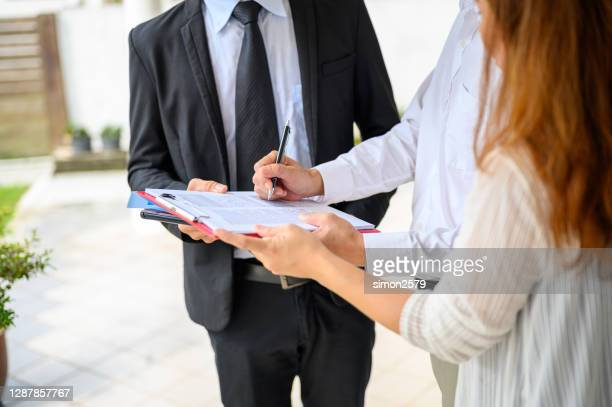 couple signing contract agreement from real estate agent in front of their new house - lease agreement stock pictures, royalty-free photos & images