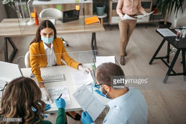 couple signing contract on meeting with insurance agent - returning stock pictures, royalty-free photos & images