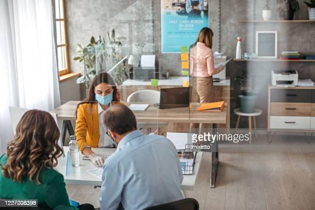 pareja firmando contrato en reunión con agente de seguros - devolución del saque fotografías e imágenes de stock