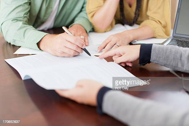 couple signing contract - mortgage stock pictures, royalty-free photos & images