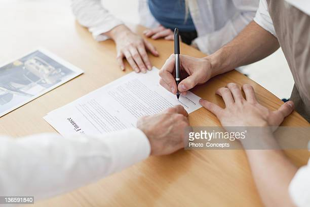 Couple signing contract with businessman