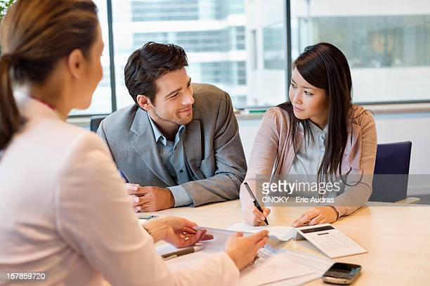 Couple signing documents with real estate agent