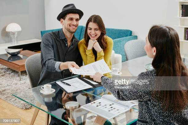 couple signing sales contract in furniture store - loan stock pictures, royalty-free photos & images