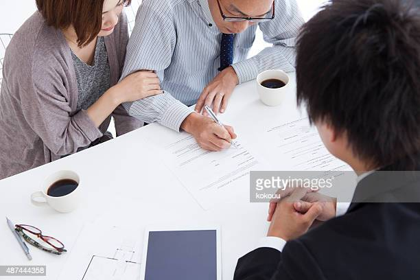 couple signing terms of real-estate contract - real estate office stock photos and pictures
