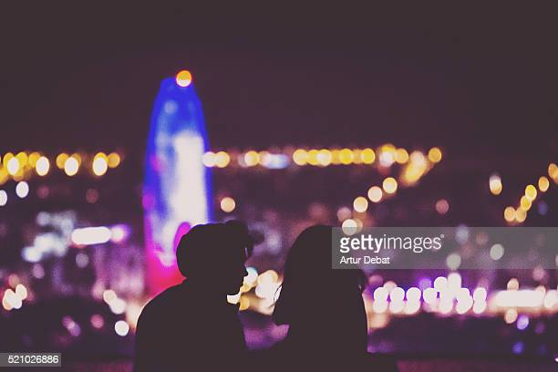 Couple silhouette by night contemplating the Barcelona city from the bunkers hill viewpoint with the bokeh city lights and the Agbar tower illuminated.
