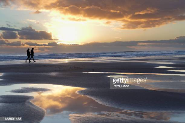 couple silhouetted on beach - conformity stock pictures, royalty-free photos & images