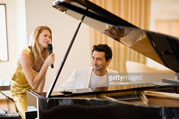 couple singing and playing piano - pianist front stock pictures, royalty-free photos & images