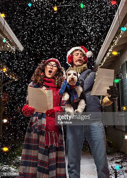 couple singing christmas carols with dog - christmas music stock pictures, royalty-free photos & images