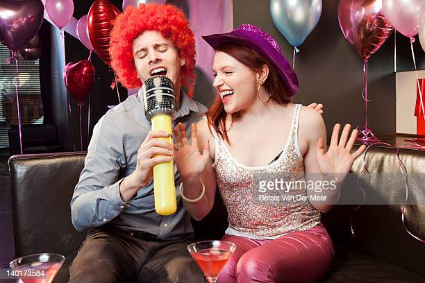 couple singing karaoke. - big mike stock pictures, royalty-free photos & images