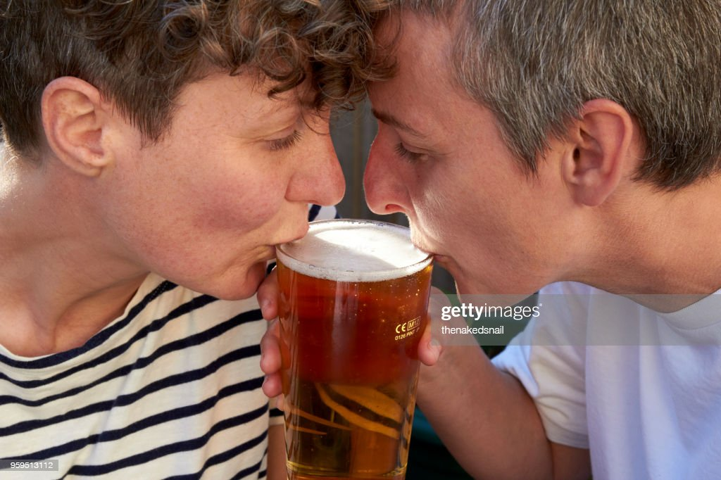 Couple sipping beer from one glass : Stock-Foto