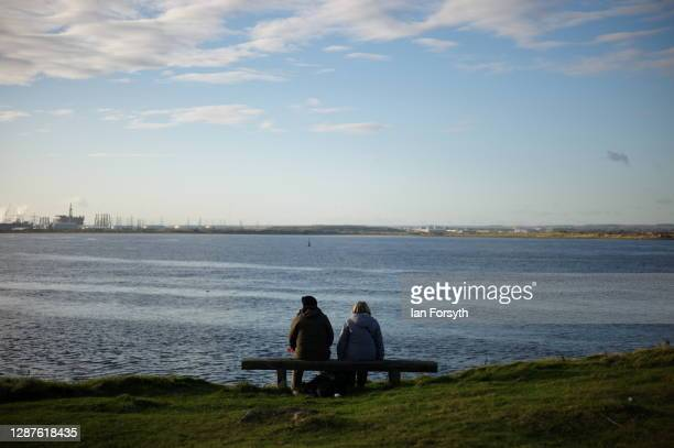A couple sit and look out over the River Tees from South Gare on November 25 2020 in Redcar England