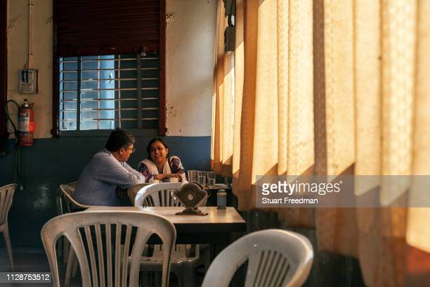 Couple sit and talk Customers in the Indian Coffee House in Nagpur, India, shielded by thick curtains from the afternoon sun. The Indian Coffee...
