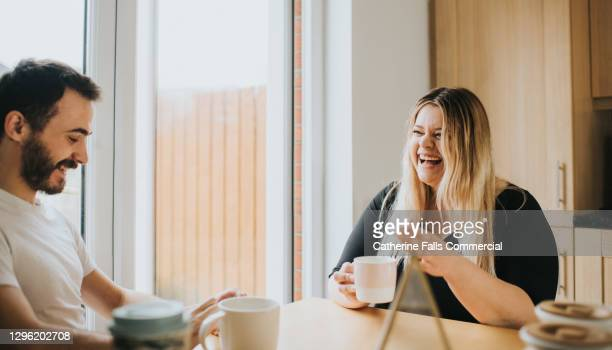 couple sit at a dining table and enjoy hot drinks, while chatting with each other - couple relationship stock pictures, royalty-free photos & images