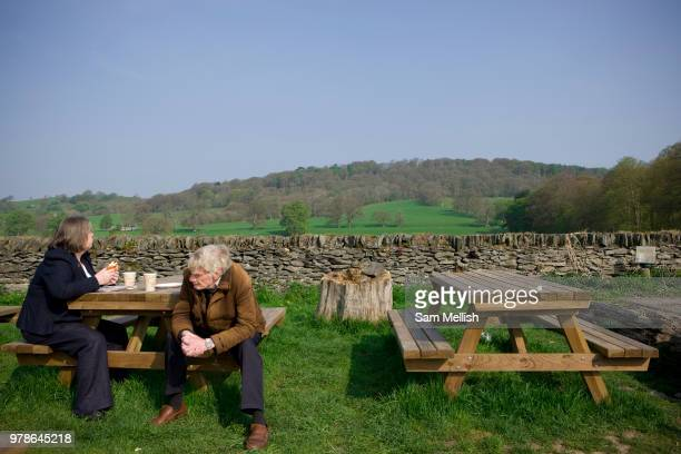 A couple sit at a picnic bench in the grounds of the rural Rhug Organic Farm Cafe on the 20th April 2011 in Corwen in the United Kingdom