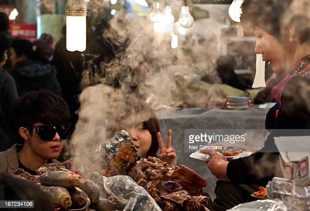 Couple sit at a Sundae stall inside Gwangjang's covered food court in central Seoul.