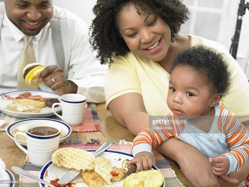 Couple Sit at a Table Having Breakfast With Their Toddler : Stock Photo