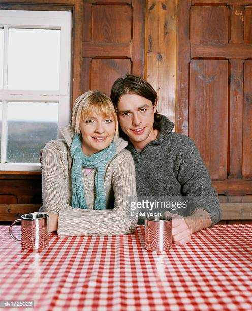 Couple Sit at a Table, Man With His Arm Around the Woman