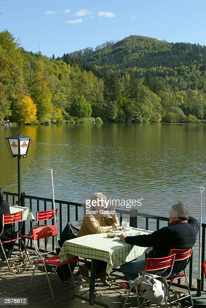 A couple sit at an outdoor restaurant on the Thalersee Lake October 10 2003 near the village of Thal Austria According to local legend Schwarzenegger...